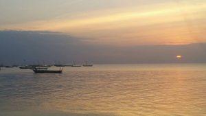 Die Sonne geht im Meer unter auf Sansibar, im Vordergrund kleinere Boote